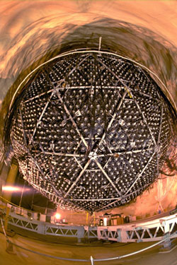 Shown here under construction, the heart of the Sudbury Neutrino Observatory is a sphere 12 meters in diameter, surrounded by almost 10,000 photomultiplier tubes to catch the faint flashes of Cerenkov radiation that mark the passage of neutrinos through the heavy water filling the sphere.
