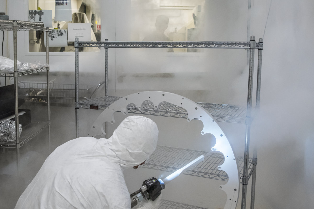 Photo - Mechanical Engineer Joe Wallig prepares a metal ring component of the injector gun for installation using a jet of high-purity dry ice in a clean room. (Credit: Marilyn Chung/Berkeley Lab)