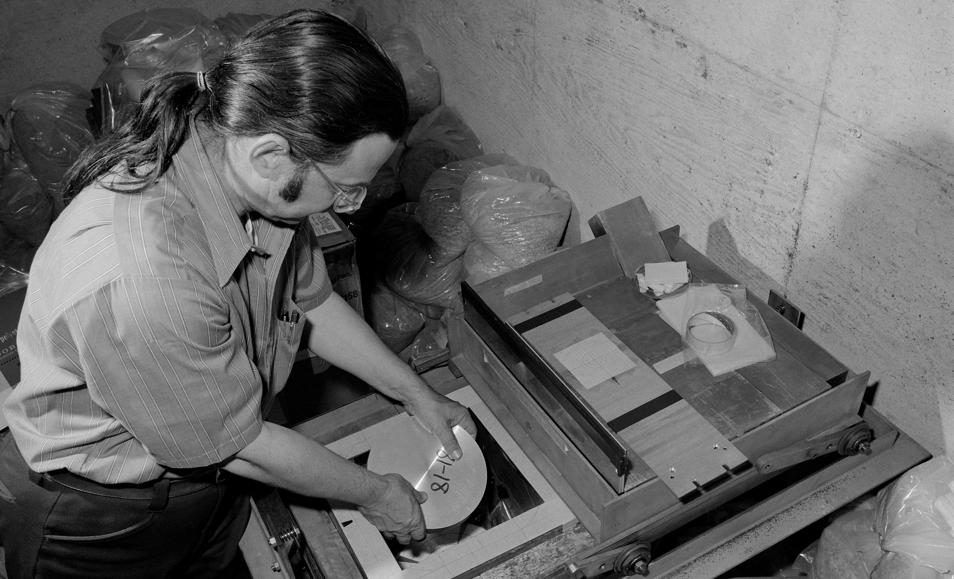"Photo - Alan ""Al"" Smith places an aluminum sample exposed to radiation at Berkeley Lab's Bevatron accelerator into a lead and concrete box containing a detector at a low-level radiation counting facility in this 1950s photograph. (Credit: Berkeley Lab)"